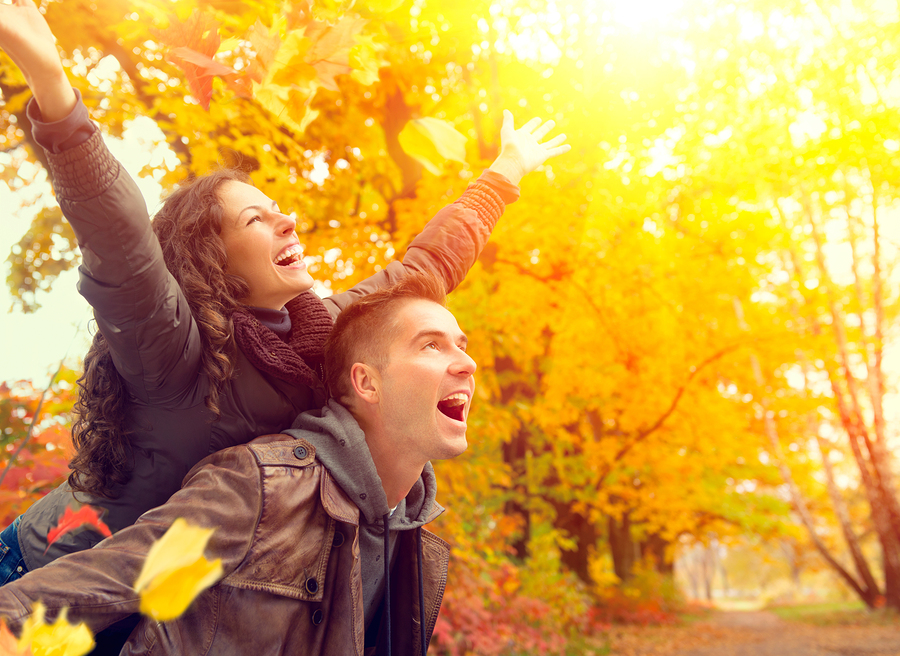 Happy Couple in Autumn Park. Fall. Young Family Having Fun Outdo